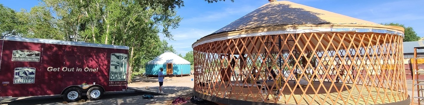 Two yurts. In the back: one constructed - turquoise. In the foreground: one during construction with exposed lattice. On the left trailer from Colorado Yurt Company.